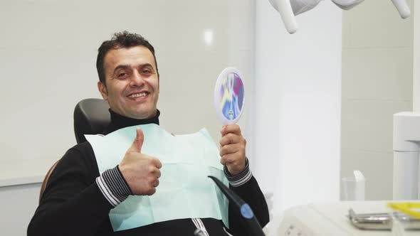 Thumbnail for Happy Mature Man Showing Thumbs Up After Dental Examination