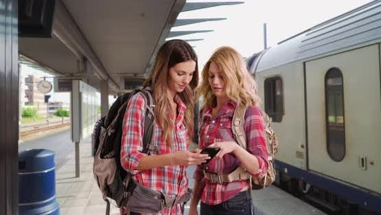 Thumbnail for Pair of female backpackers navigating destination on phone at train station