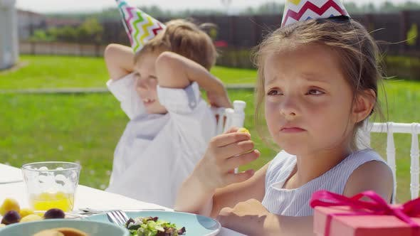 Thumbnail for Cute Kids in Party Hats Talking with Family at Dinner Table