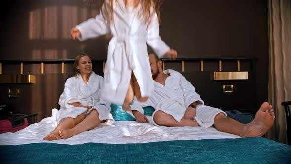 Thumbnail for A Family in White Bathrobes Sitting in the Bed - a Girl Jumping on the Bed