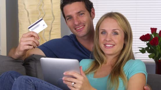 Happy couple smilng with credit card and tablet