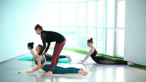 Yoga Instructor Teaches Woman Cobra Pose  Asana Bhujangasana