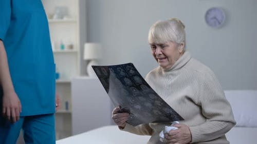 Nurse Supporting Crying Old Woman Looking at Brain Roentgen, Fatal Diagnosis