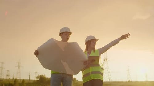 Two Engineers a Man and a Woman in Helmets with a Tablet of Engineer Walk on Field with Electricity