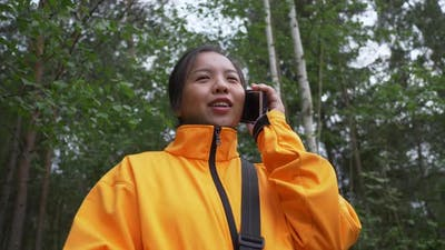 Happy Asian woman taking a call in the forest