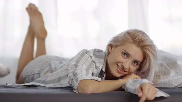 Thumbnail for Caucasian Blonde with Seductive Gaze Lying on Bed in Pajamas