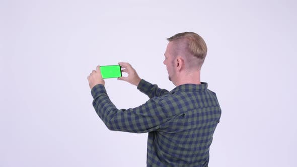 Thumbnail for Rear View of Blonde Hipster Man Taking Picture with Phone