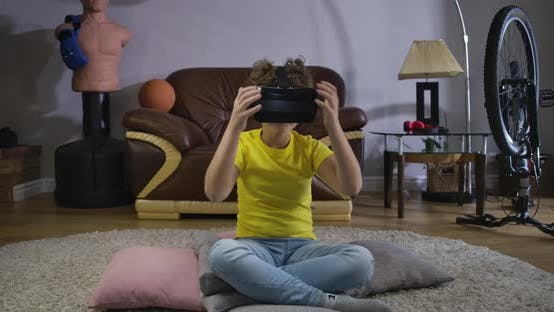 Portrait of Teenage Caucasian Boy in VR Headset Sitting on the Floor at Home and Looking Around