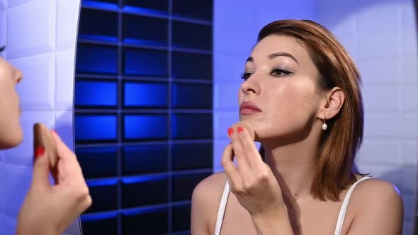 Young and Beautiful Woman Applying Makeup with a Sponge.