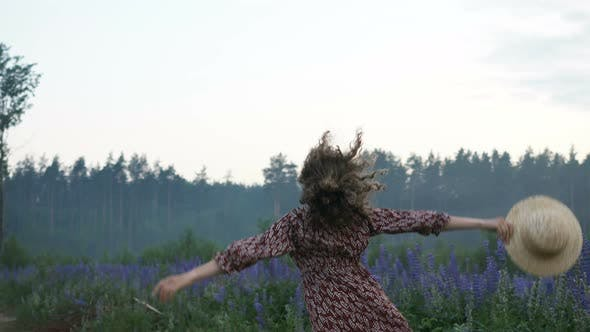 Thumbnail for Slim Girl Jumps and Dances with Joy By Field of Fresh Lupins