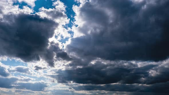 Timelapse of Gray Cumulus Clouds Moves in Blue Sky. Sun Rays Shine. Cloudspace
