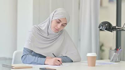 Pensive Young Arab Woman Writing on Paper