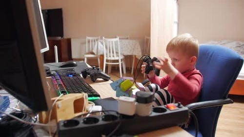 Little Boy Playing On Computer With Joystick