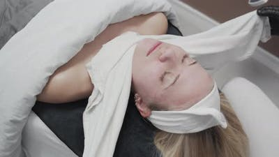 Woman'S Face Being Cleaned With Material In Salon