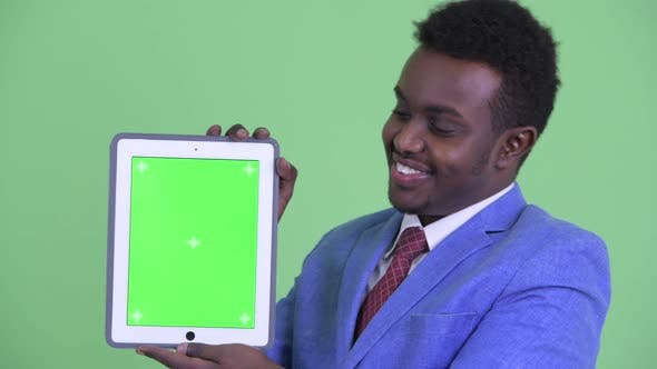 Cover Image for Face of Happy Young African Businessman Showing Digital Tablet