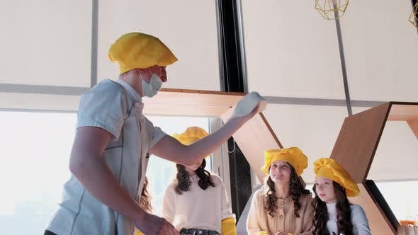Children in yellow hats help to cook pizza in the kitchen.