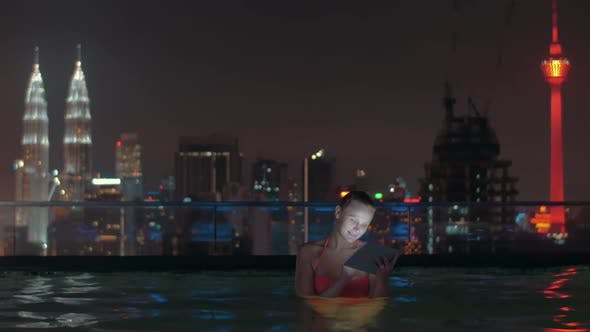 Thumbnail for Woman with Pad in Rooftop Pool of Night Kuala Lumpur