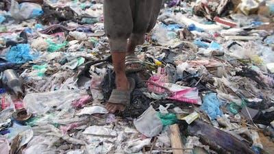 Poverty Boy's Legs Walking On Garbage Dump