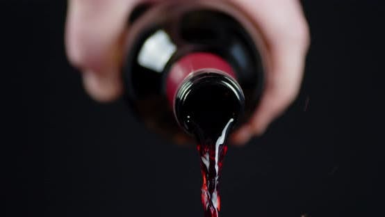 A Man's Hand Holds a Bottle of Pouring Wine.
