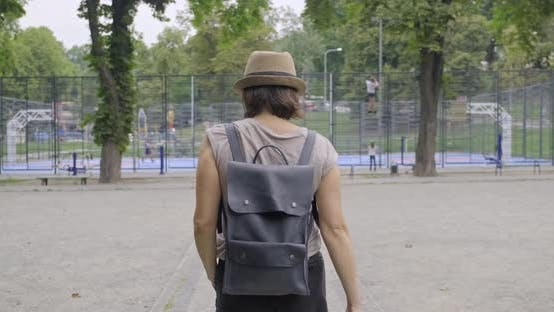Thumbnail for Woman Walking with His Back in Park, Background Urban Sports Field Basketball Court