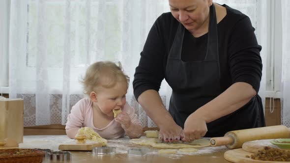Thumbnail for Granny Cutting Cookies of Raw Gingerbread Dough and Granddaughter Tastes Dough.