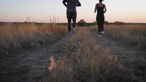 Couple Running at Sunset. Outdoor Sports.