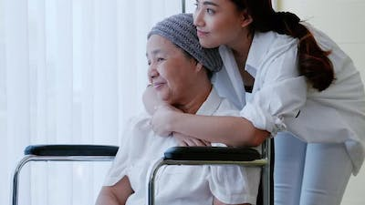 The daughter encourages and comforts a mother with cancer during hospitalization.