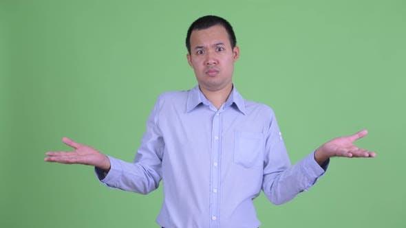 Thumbnail for Confused Asian Businessman Shrugging Shoulders