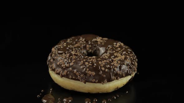 Thumbnail for Delicious Melted Dark Chocolate Syrup Pouring Over a Donut on Black Background