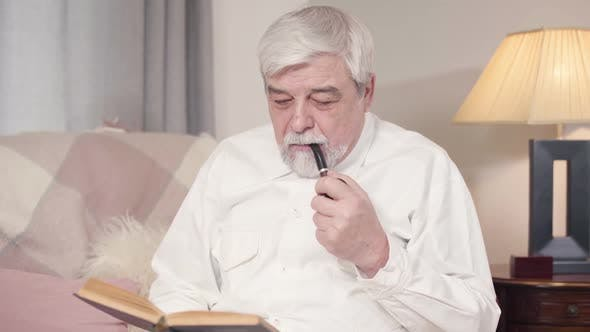 Cover Image for Portrait of Grey-haired Caucasian Man Smoking Pipe and Reading Book at Home. Mature Serious Man