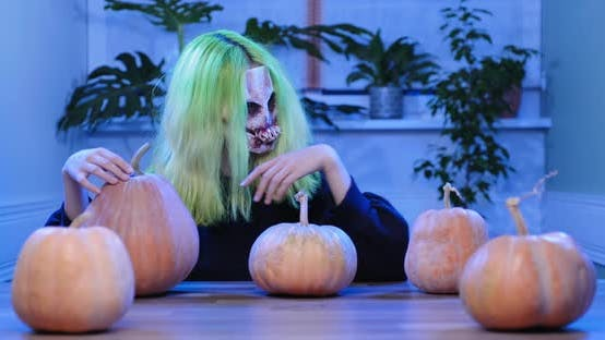 Halloween Day. Young Woman in Horrible Mask with Pumpkins