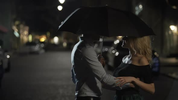 Cover Image for Beautiful Couple of Lovers Embracing Under Umbrella Night Date Love Story