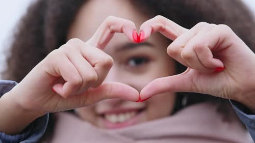 Head Shot Close Up Smiling Kind Afro Woman Showing Heart Symbol To Camera Makes Gesture of Love