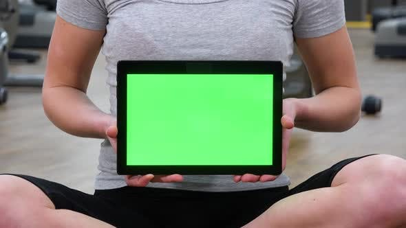 Cover Image for Closeup on a Tablet with a Green Screen a Woman Holds in a Gym