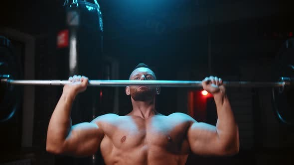 Tough Man Standing in the Gym and Lifts a Heavy Bar and Pumping His Hands Muscles Over His Head