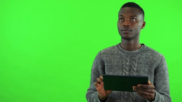 Thumbnail for A Young Black Man Works on a Tablet with a Smile - Green Screen Studio
