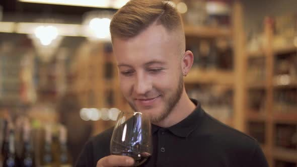 Thumbnail for Male Visitor To a Liquor Store Takes the Offered Wine Glass and Sniffs the Aroma of the Wine