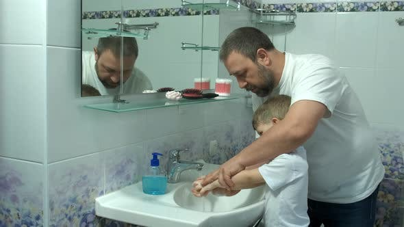 Dad washes a small child's hands with soap over the sink with running water. Personal hygiene