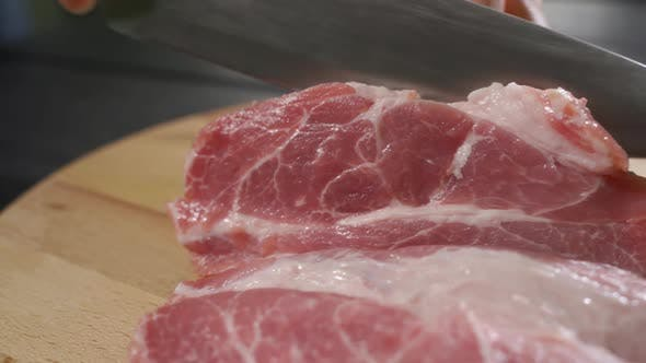 Cover Image for The Chef Cuts Raw Meat with the Knife in Slow Motion