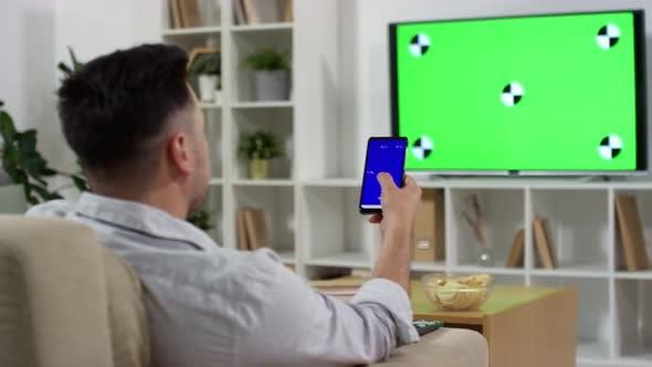 Thumbnail for Mann Fernsehen mit grünem Bildschirm und mit Smartphone zu Hause