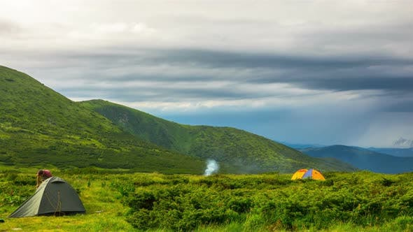 Couple Setting up Camp Tent in the Mountains