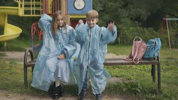 Thumbnail for Cute Children Sitting on Bench on Playground and Putting on Raincoat Hoods