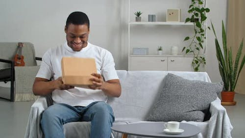 Curious African American Male Consumer Recipient Sitting at Home Receives Parcel with Gift