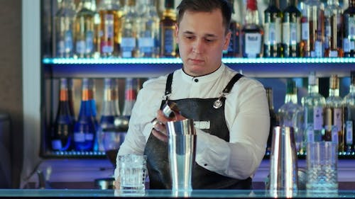 Bartender makes a cocktail at the bar, pours to a glass from shaker