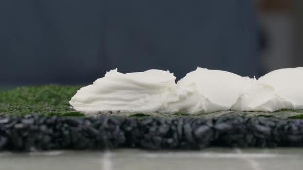 Thumbnail for Sushi-Chef fügt etwas Creme-Käse auf die Sushi-Rolle in Zeitlupe, der Koch bringt Käse auf die Nori