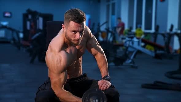 Hübscher Power athletischer Mann Bodybuilder macht Übungen mit Hantel.