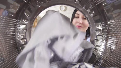 Young Woman Takes Clean Laundry Out of the Washing Machine