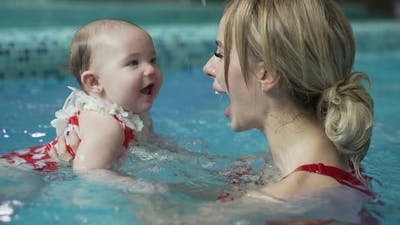 Cheerful Mother with Her Baby in the Pool