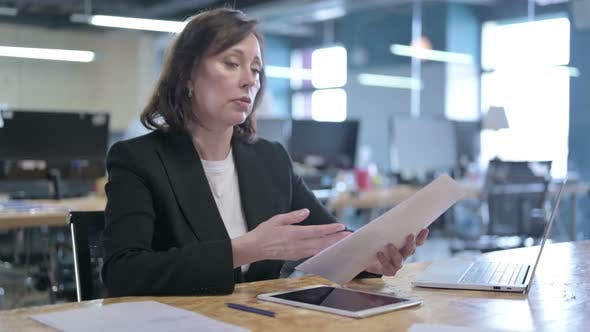 Thumbnail for Serious Middle Aged Businesswoman Reading Paper and Talking While Sitting in Office