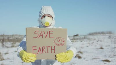 Man Wore in Protective Suit Shows Save Earth Sign on Abandoned Place in Winter